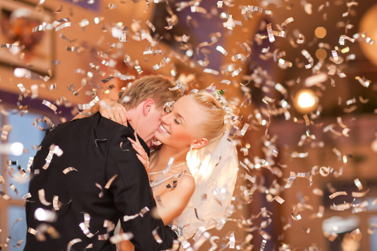 Beautiful couple first dance in flying confetti